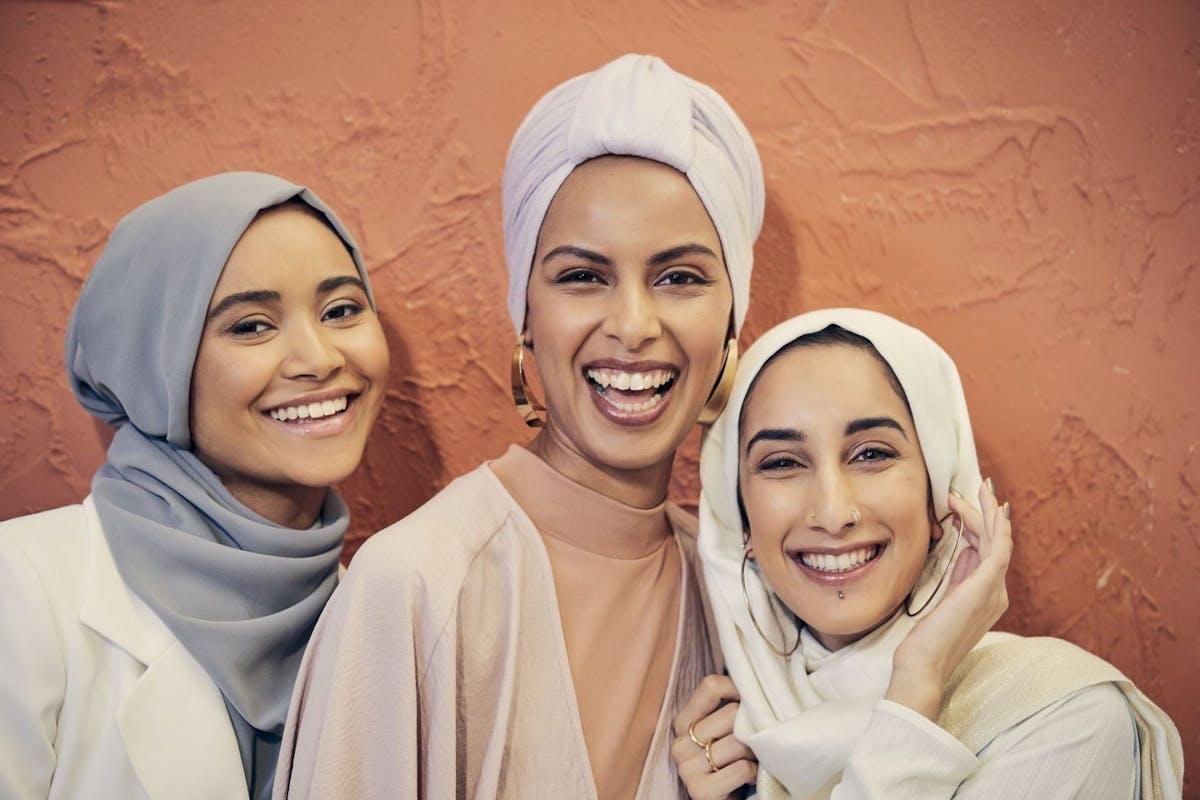 three hijabi women smiling at camera