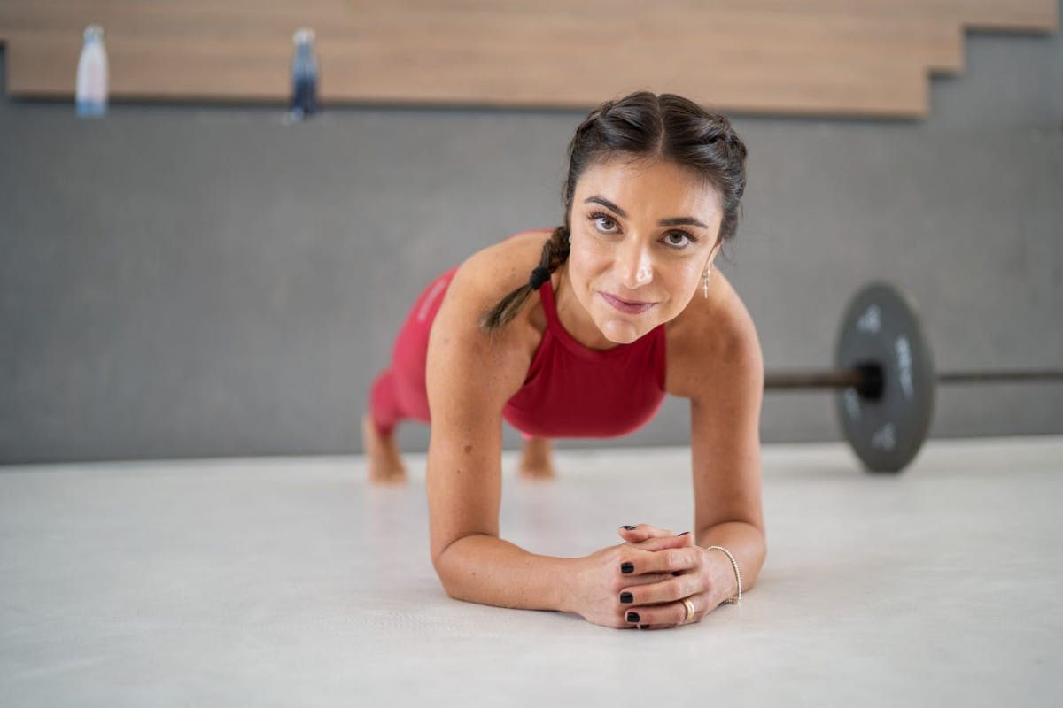 A woman doing a plank on the gym floor with a barbell behind her