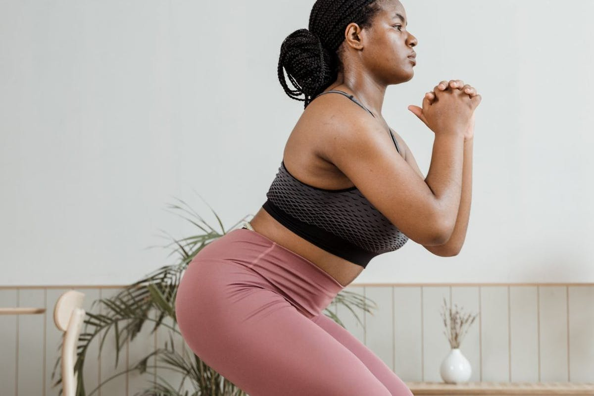 A woman doing a squat in her living room while working out from home