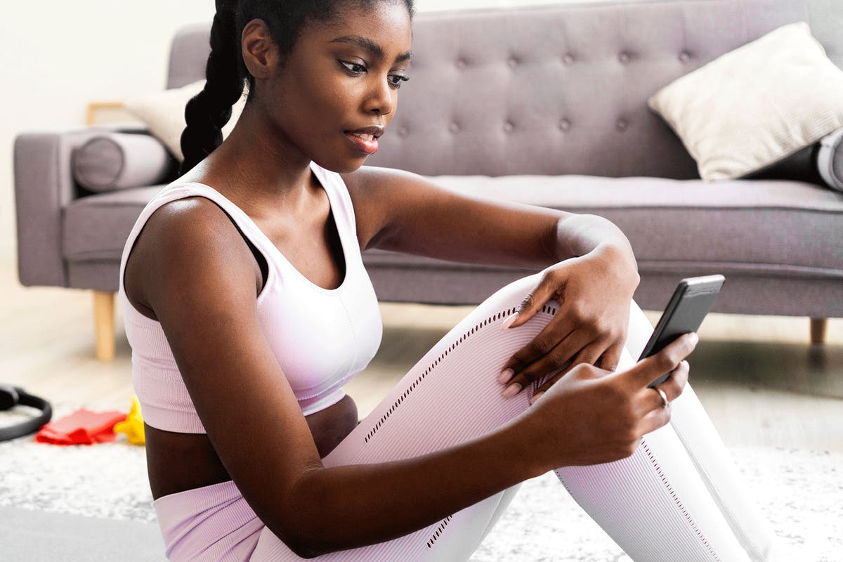 A woman texting on her phone while sat on the floor during a home workout
