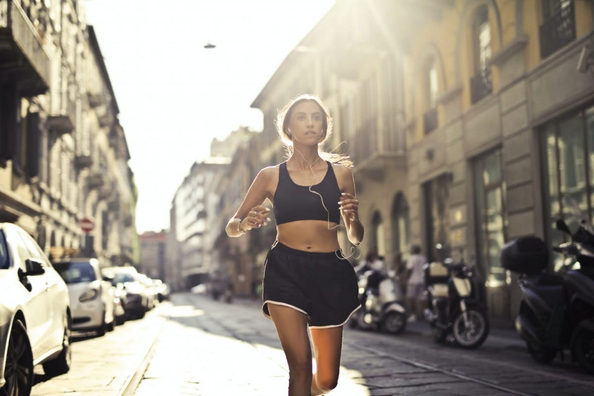 A woman in thought while running through a city street