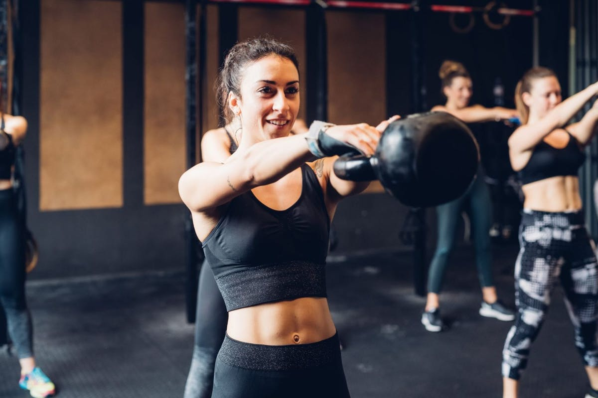 Smiling woman in gym lifting