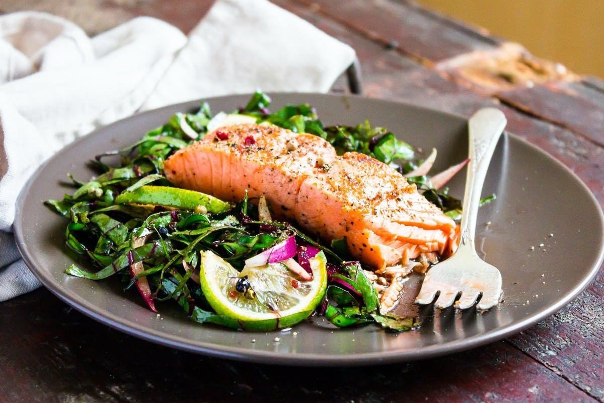 Salmon on a bed of green salad on a grey plate.