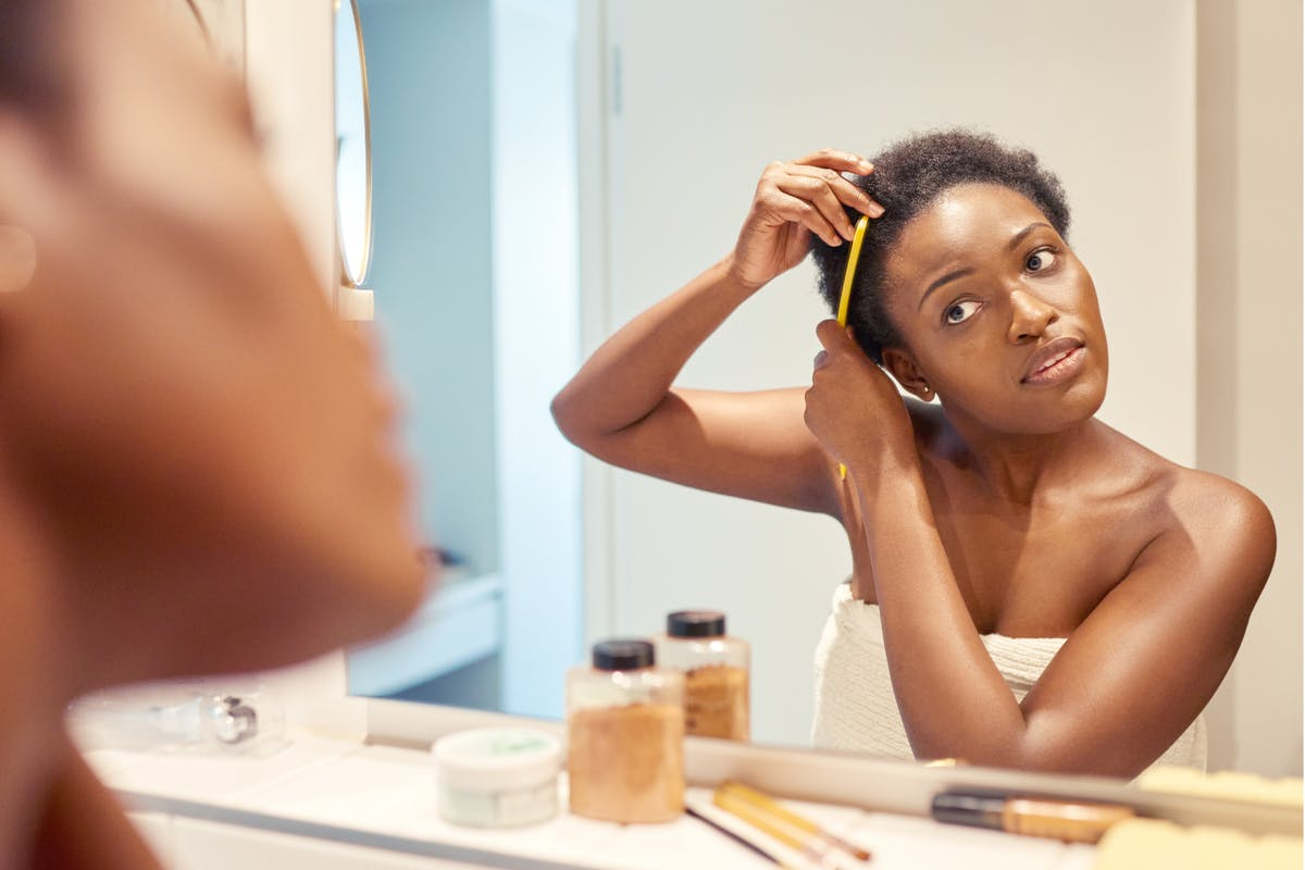 Woman styling afro hair in mirror