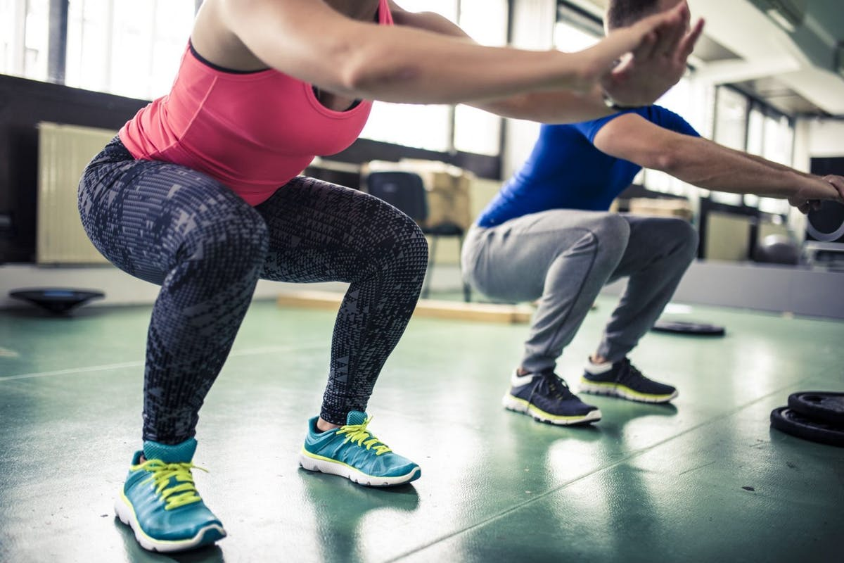 Woman wearing blue trainers, patterned leggings and pink top performing a squat in a gym studio.