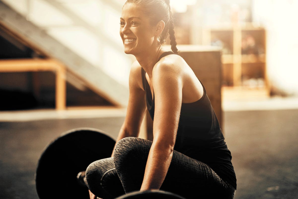 A woman smiling at a barbell