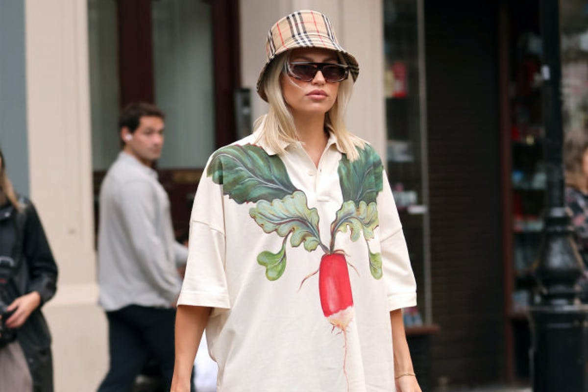 A woman wearing a printed shirt with Burberry hat