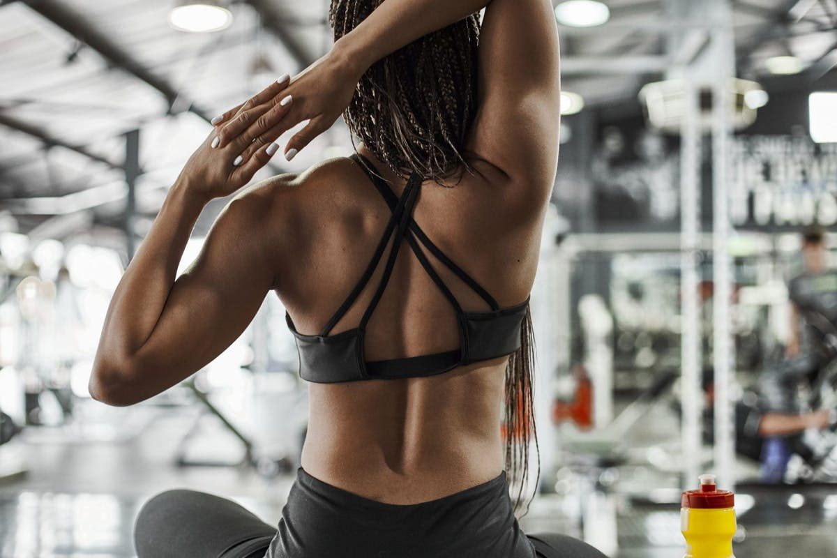 A woman stretching her upper body in the gym