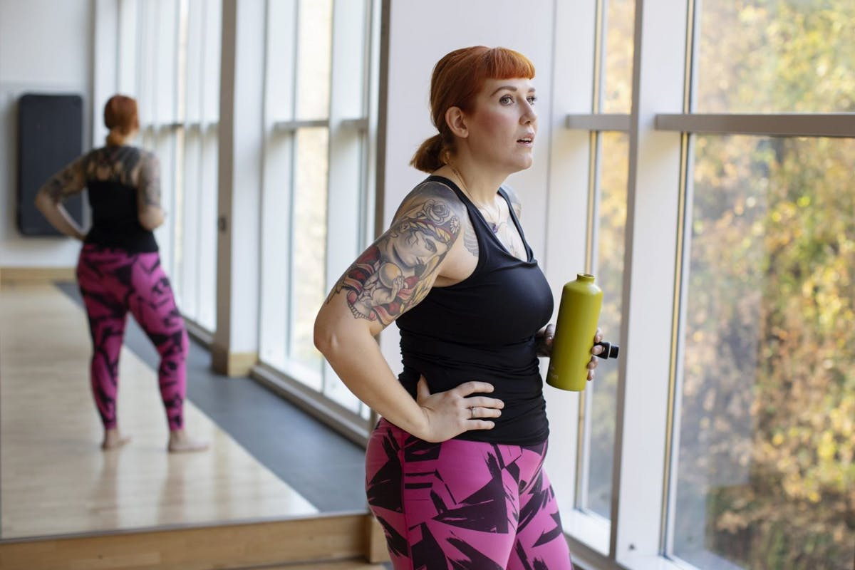 A woman looking away from a mirror in a gym