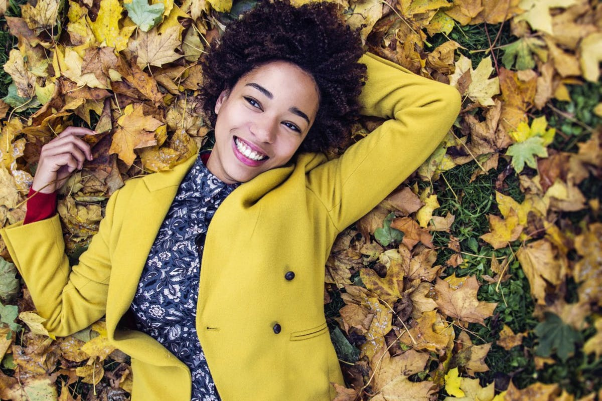 Happy smiling young woman lying down the the Autumn leaves outdoors