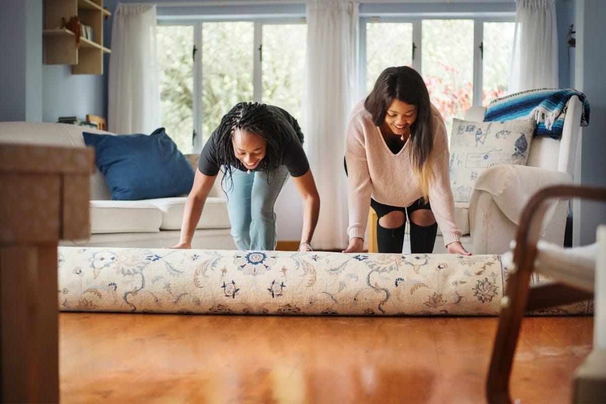 Two women unrolling a carpet