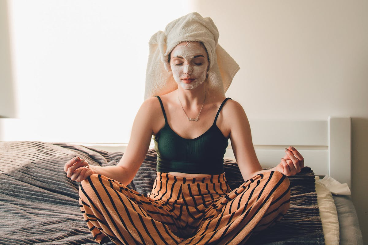 Psychodermatology woman meditating on bed with face mask