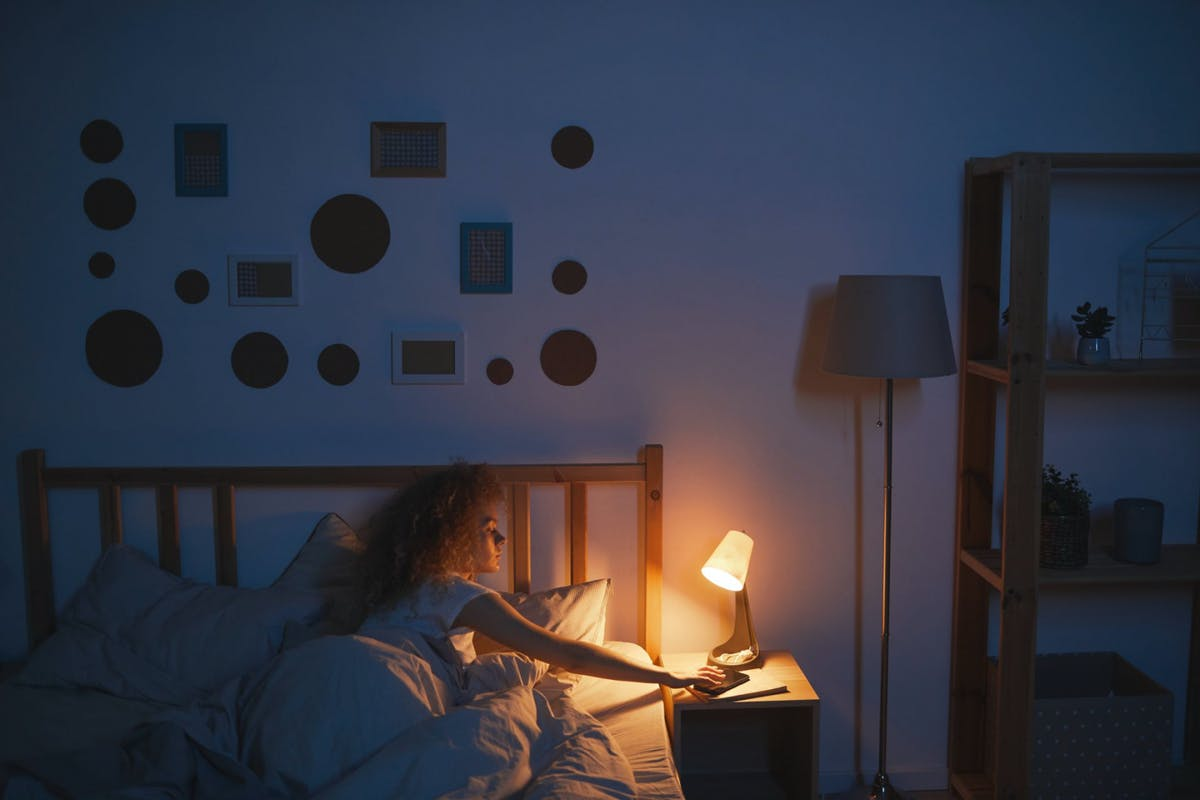 A woman switching on her lamp in the morning