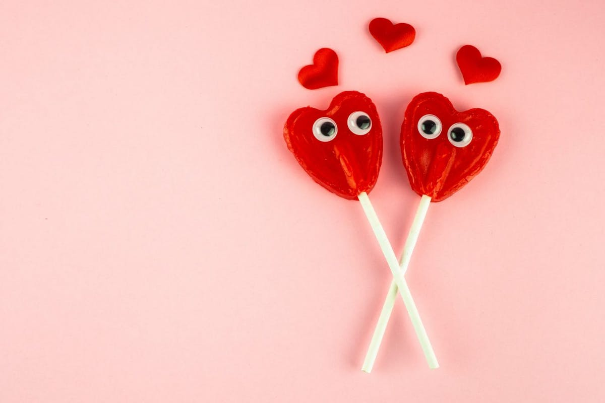 Concept of love and romanticism. Two red heart lollipops with eyes looking at each other and several red hearts - stock photo