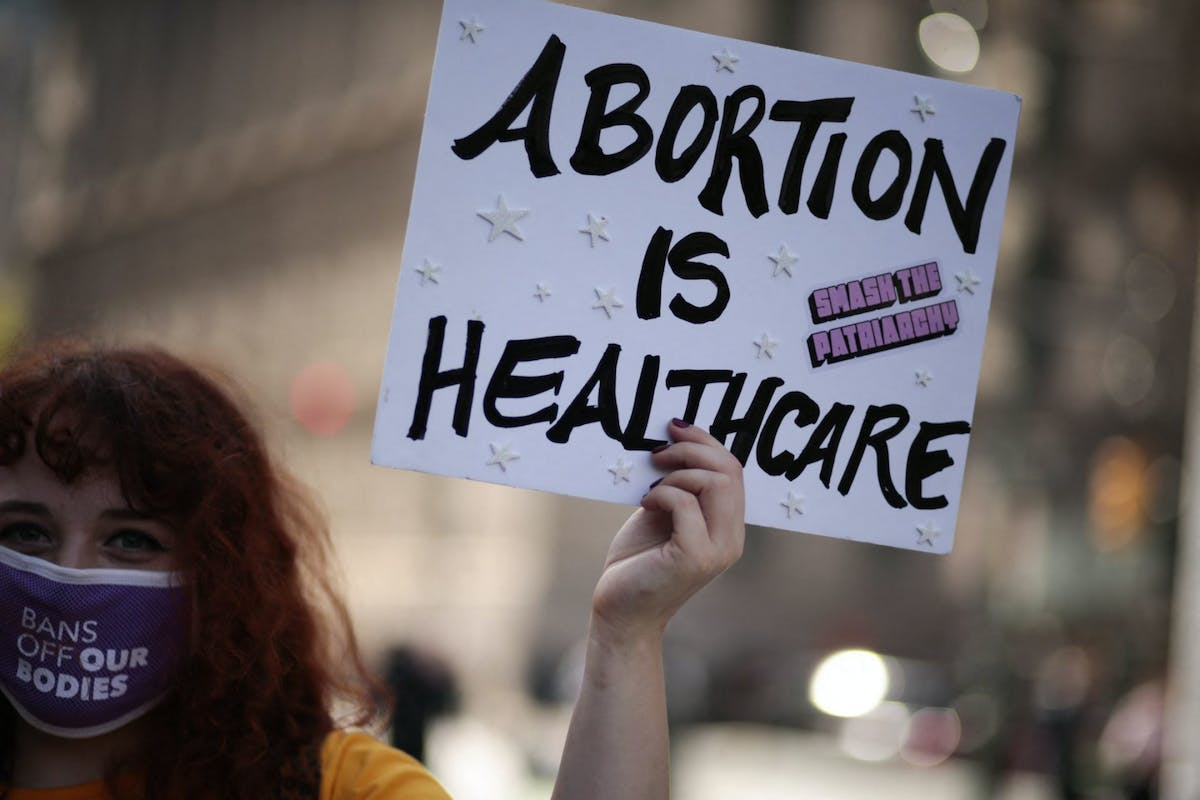 """A woman holds a sign that reads """"Abortion is healthcare"""""""