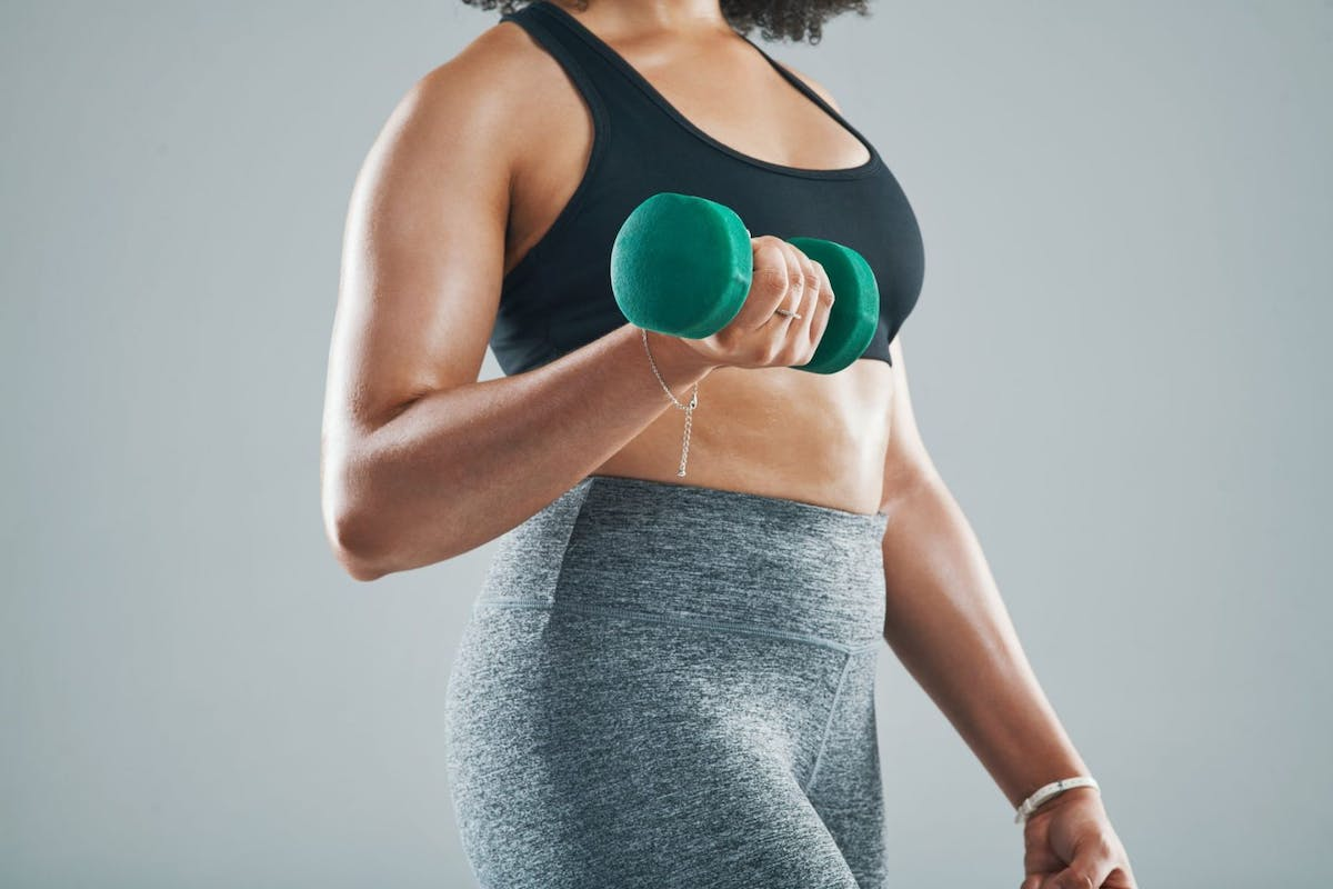 A woman lowering a dumbbell from a bicep curl