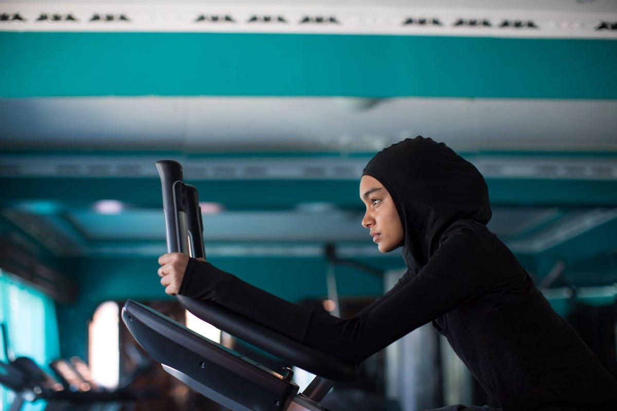 woman in hijab on exercise bike
