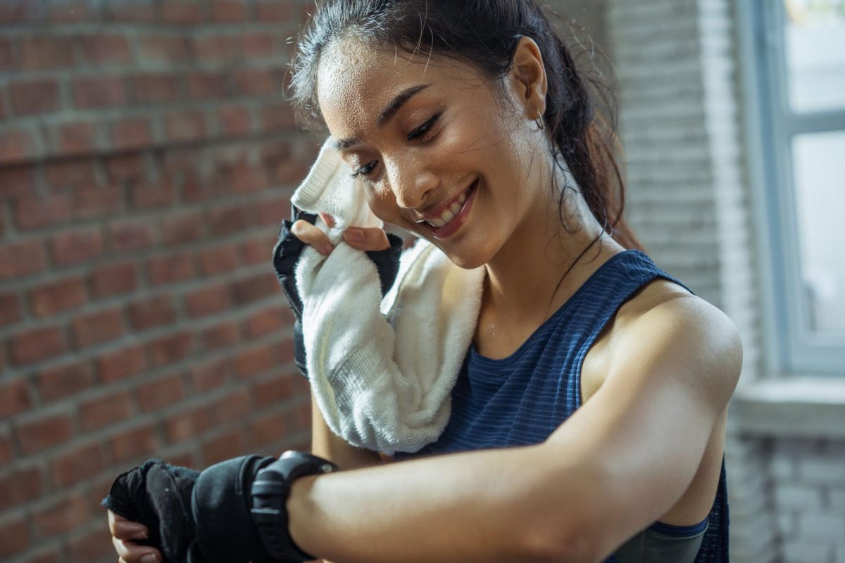 A woman wiping her sweat with a towel after a workout