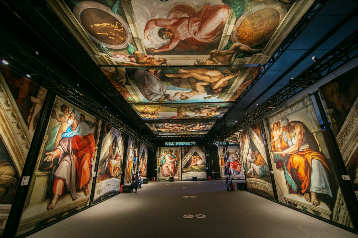 image of immersive art exhibition featuring floor-to-ceiling rendering of Michelangelo's ceiling frescoes.