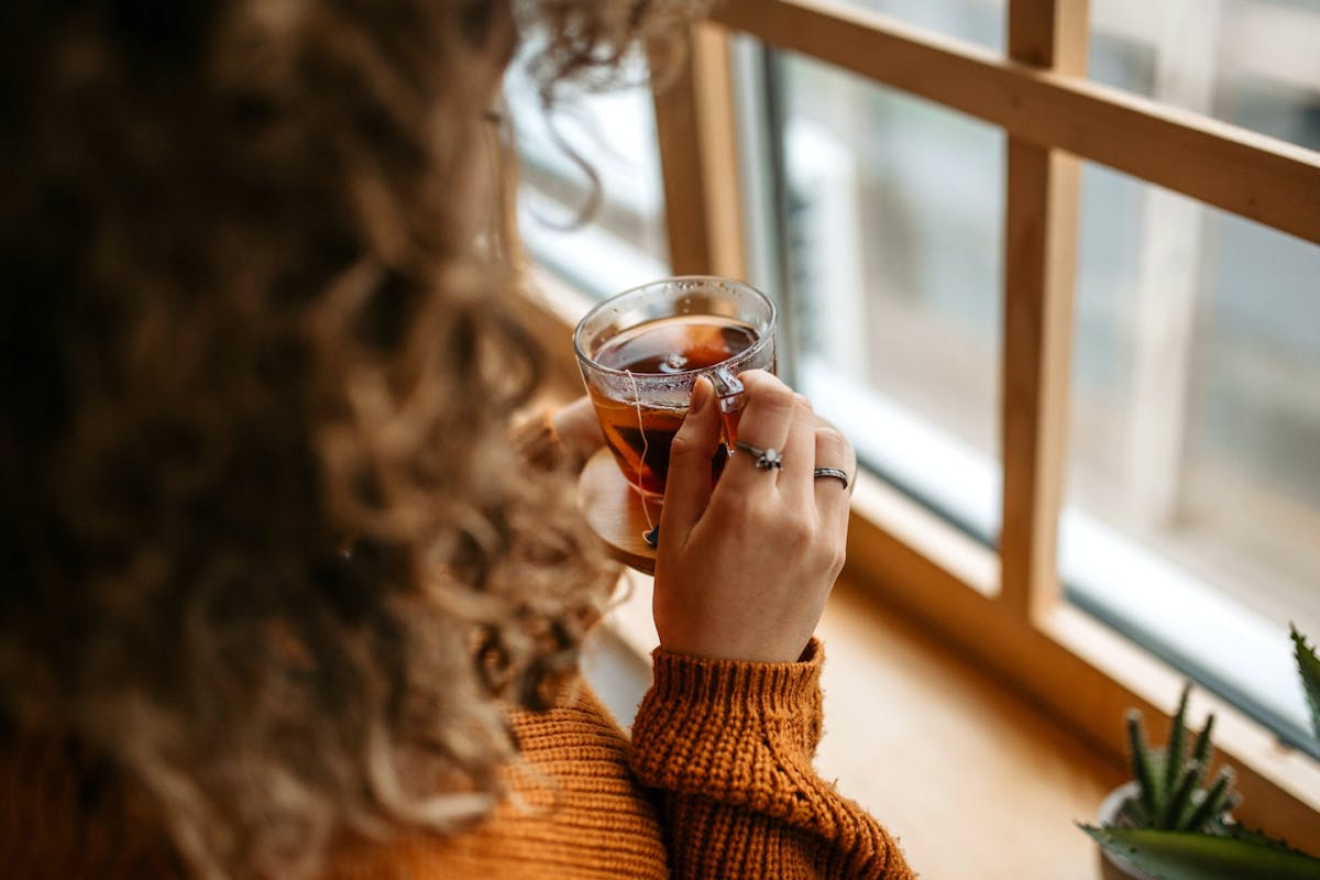 A woman holding a drink in front of the window