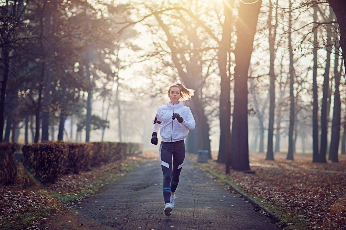woman running woods winter