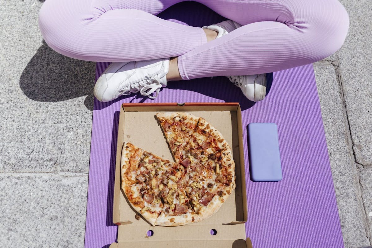 A woman eating a pizza on her yoga mat
